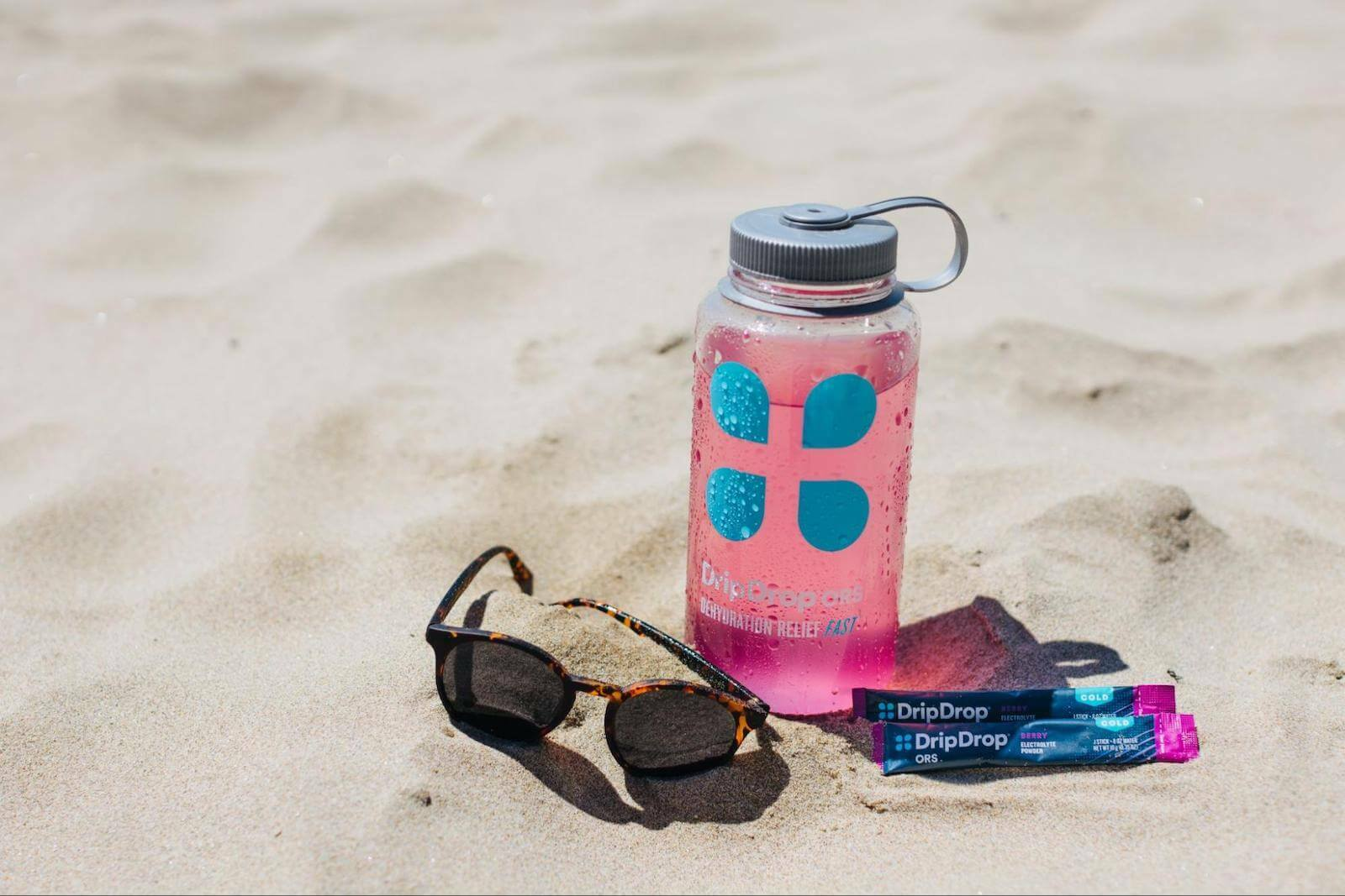 DripDrop ORS tumbler, sachets and sunglasses on the sand
