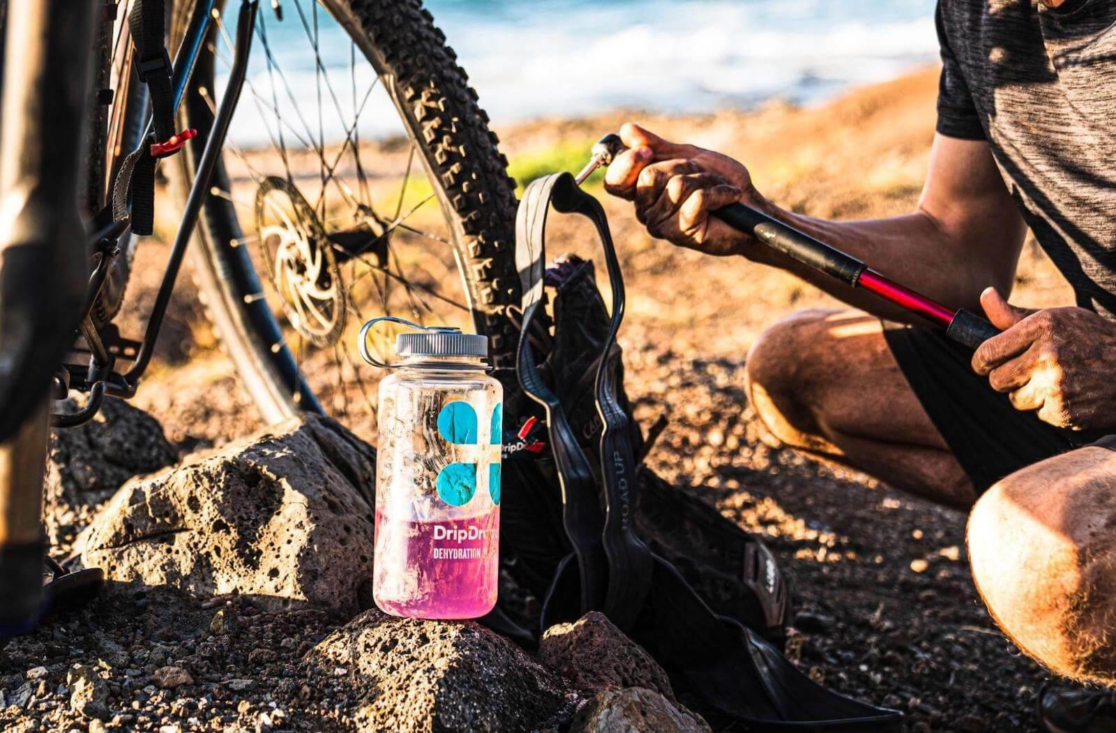 How to treat heat stroke: DripDrop tumbler beside a bike tire