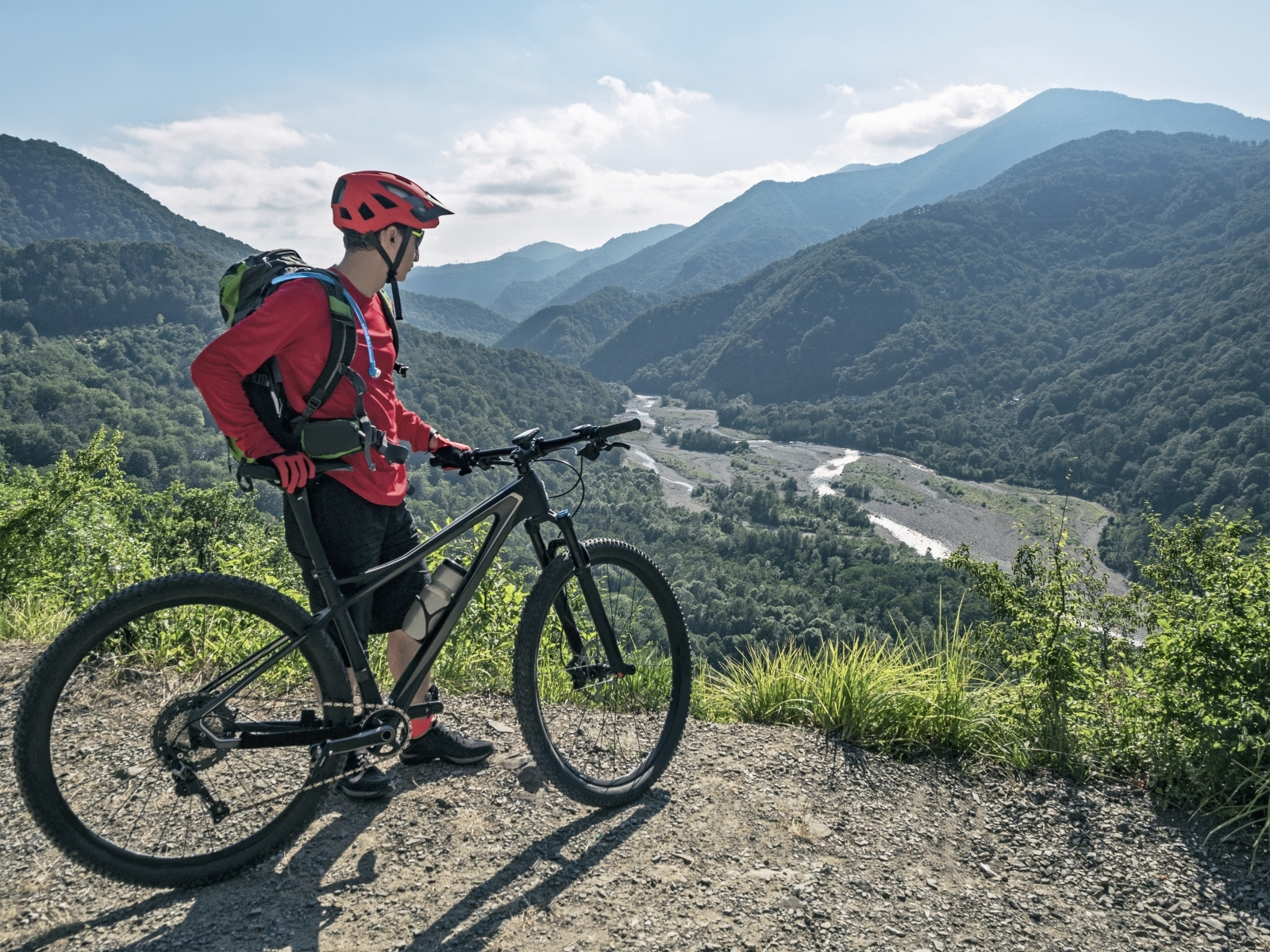 hydration bladder: Man looking down at the view after riding his mountain bike