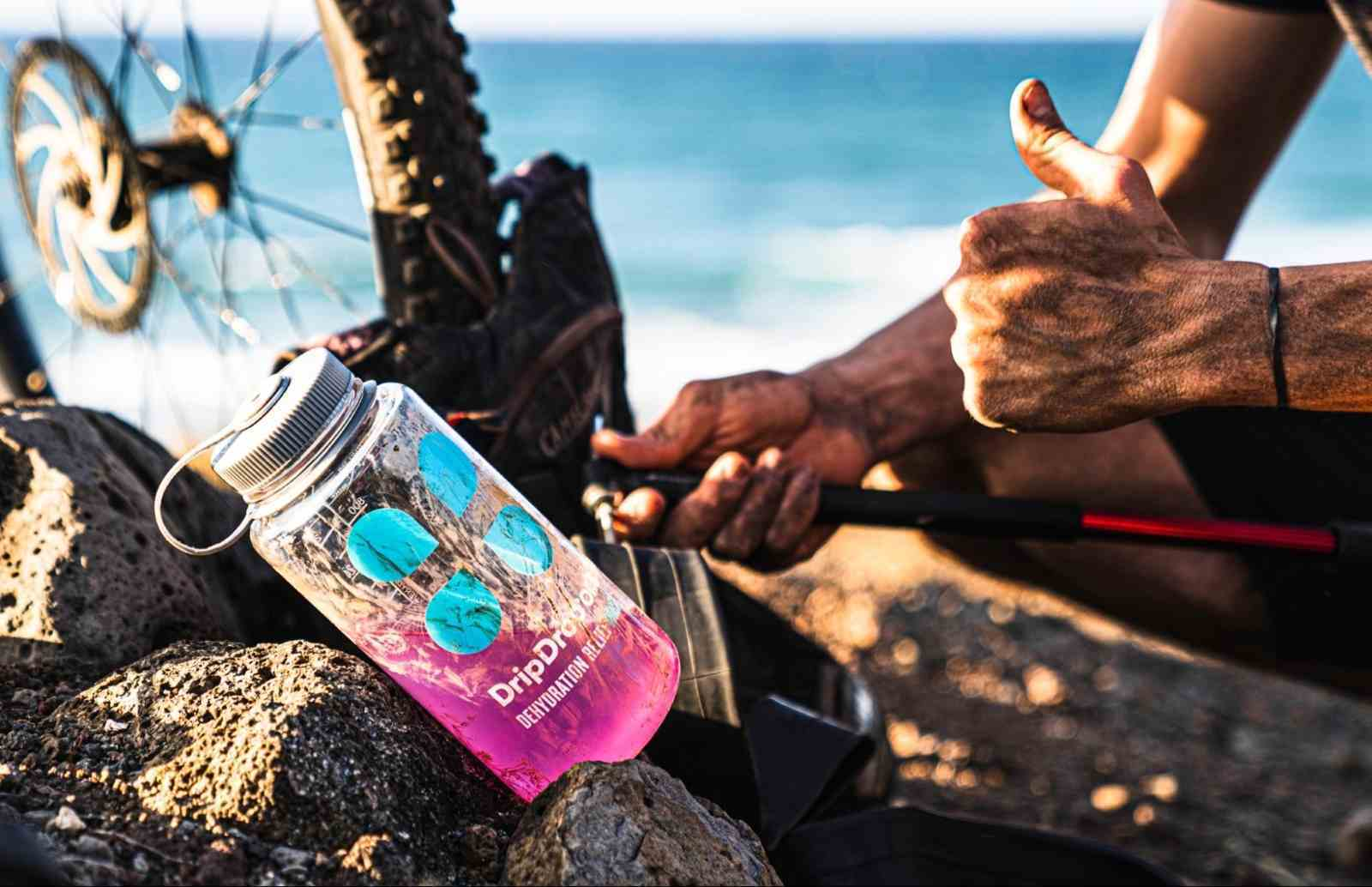 how to rehydrate: Tumbler with DripDrop ORS on top of rocks and a biker giving a thumbs up in the background