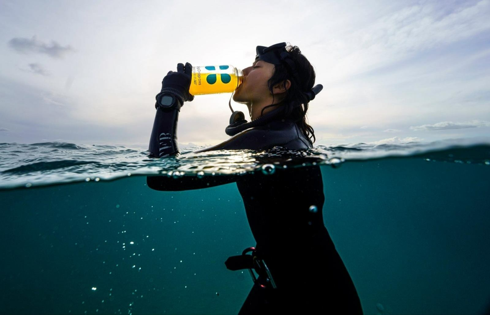 Woman drinking DripDrop ORS while in the water