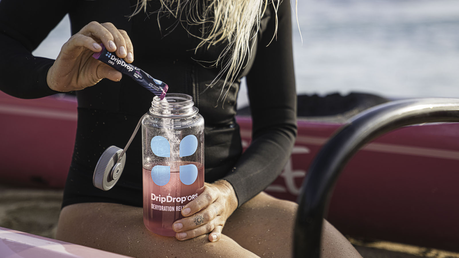 Drip Drop vs Liquid IV: Woman on paddleboat adding DripDrop to water