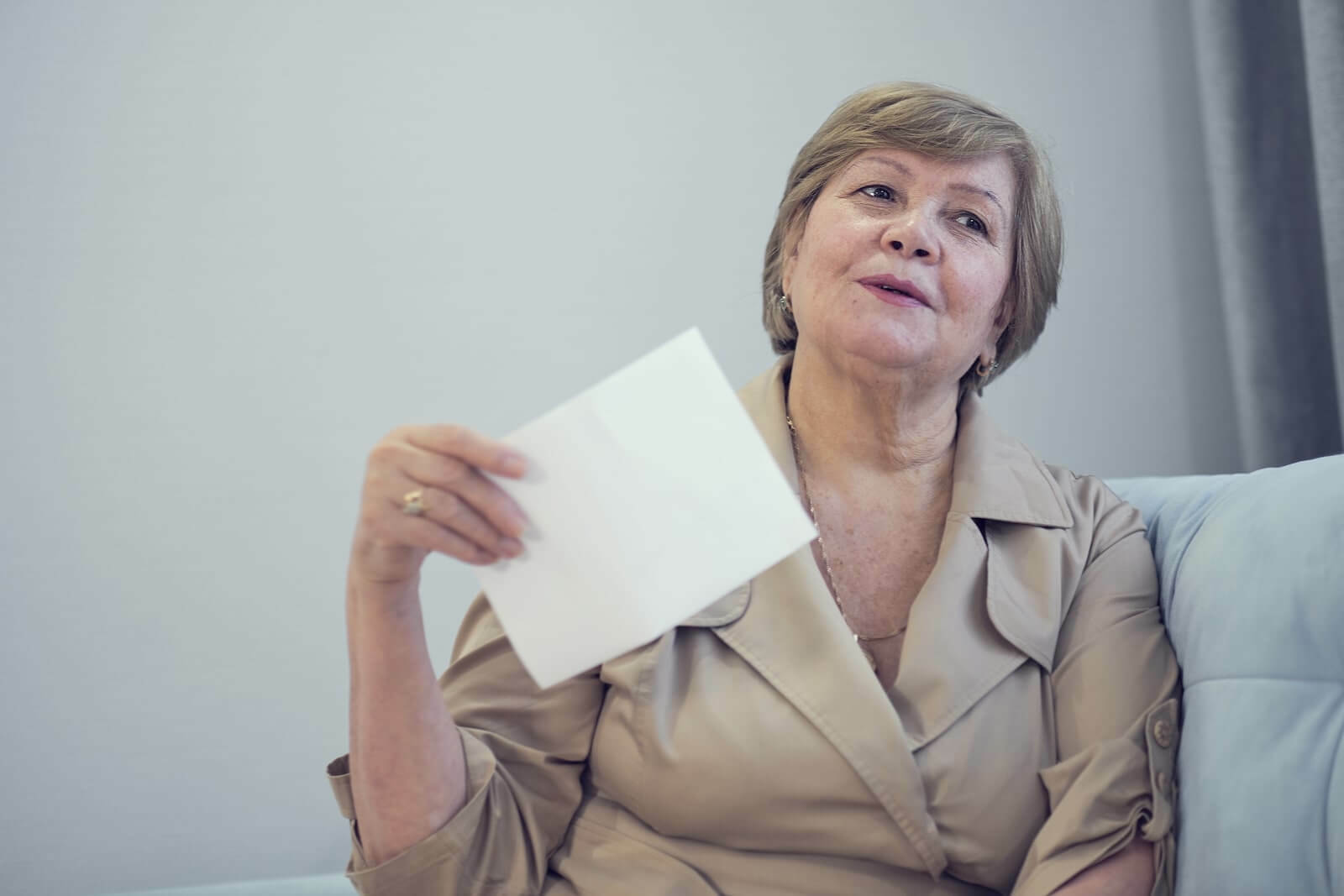 Elderly woman fanning herself with a piece of paper