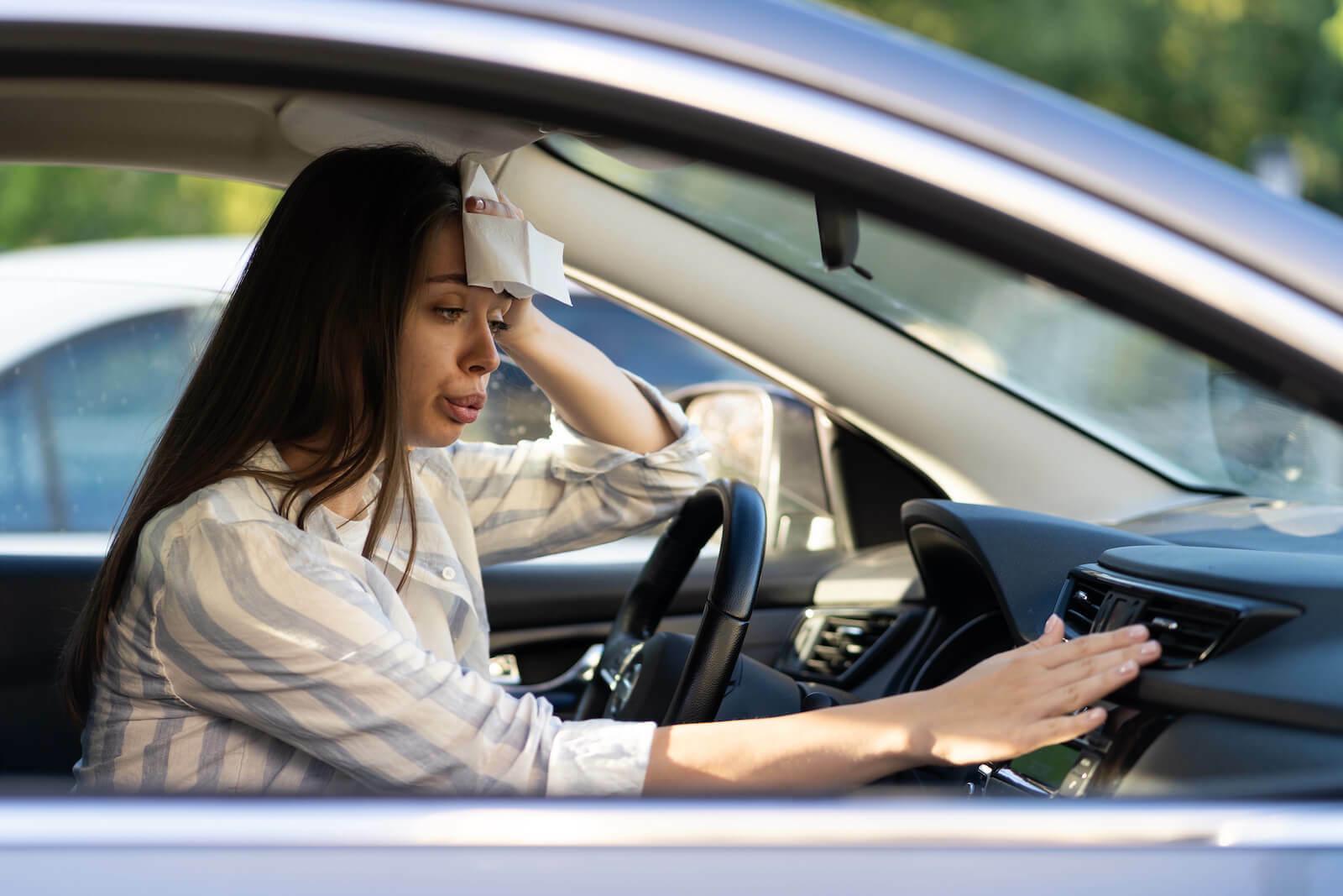 Head feels hot: woman inside her car wiping her sweat
