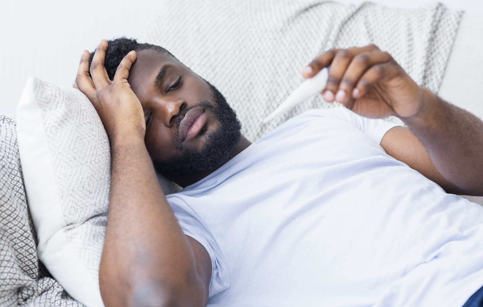 Chills and sweats: man laying in bed and checking is temperature