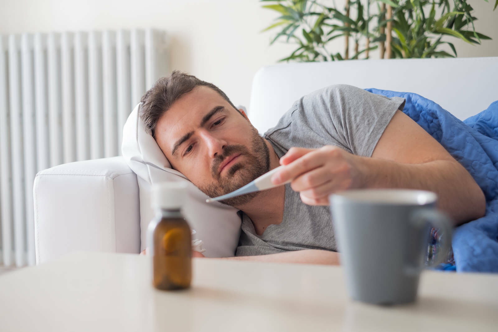 Man lying on the sofa, checking his temperature