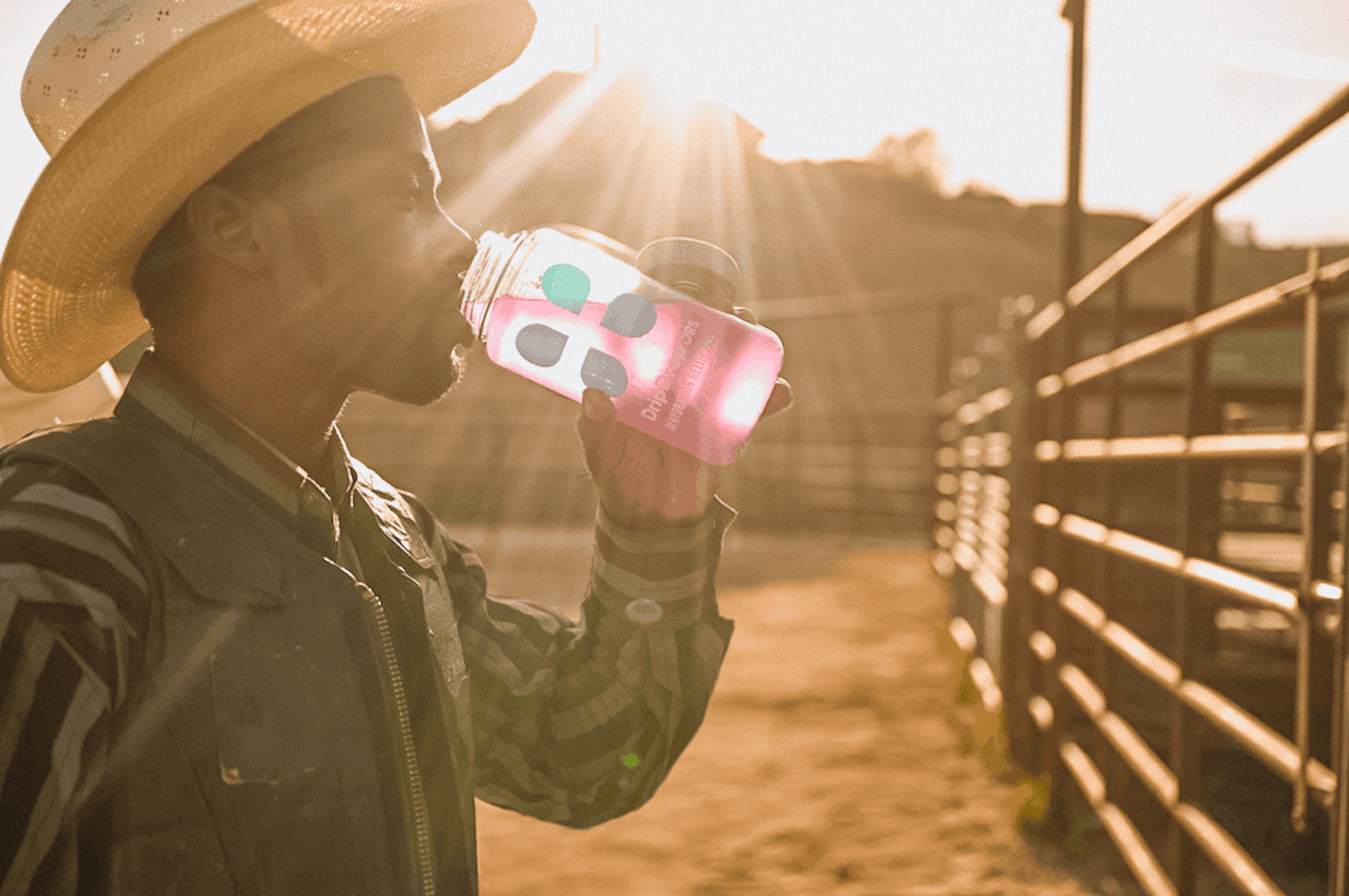 What drinks have electrolytes: man under the heat of the sun, drinking from a DripDrop ORS tumbler