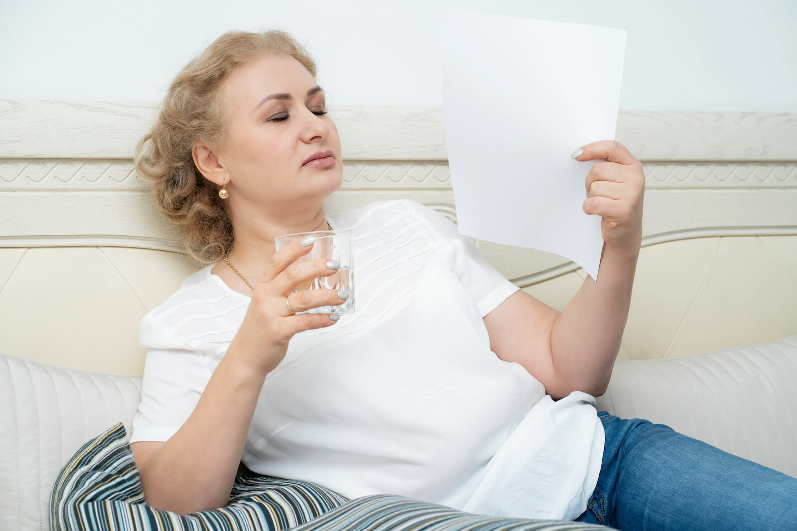 Head feels hot: middle-aged woman fanning herself