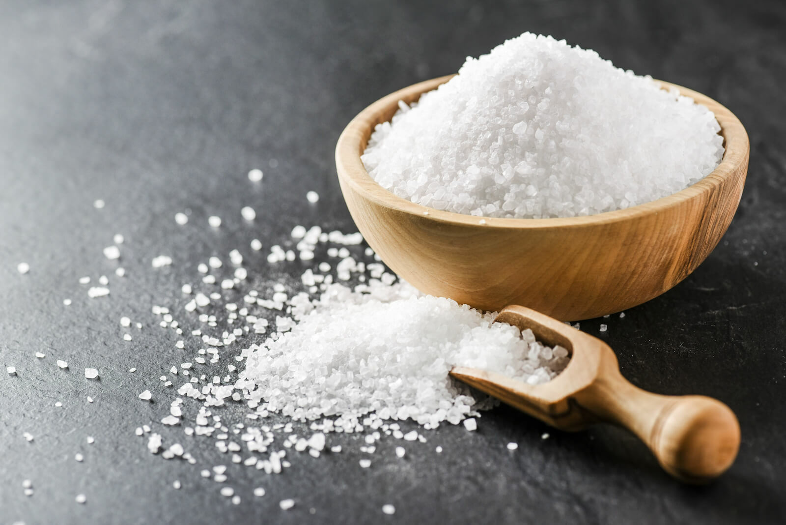 Electrolytes benefits: sea salt in a wooden spoon and bowl