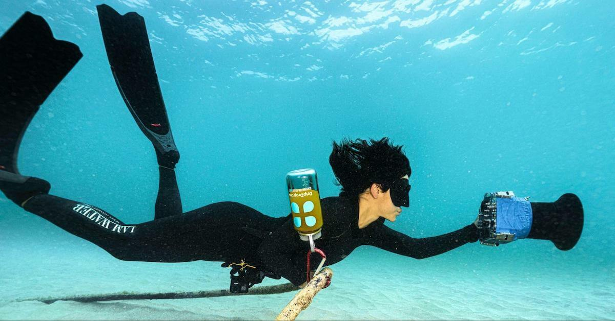 Woman underwater with a DripDrop tumbler