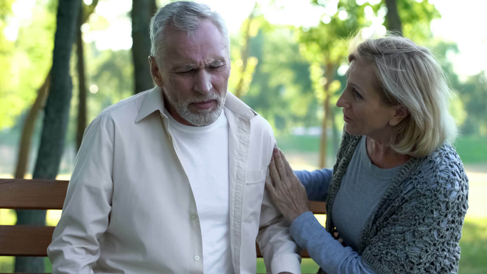 Nausea and sweating: unwell elderly man being comforted by an elderly woman