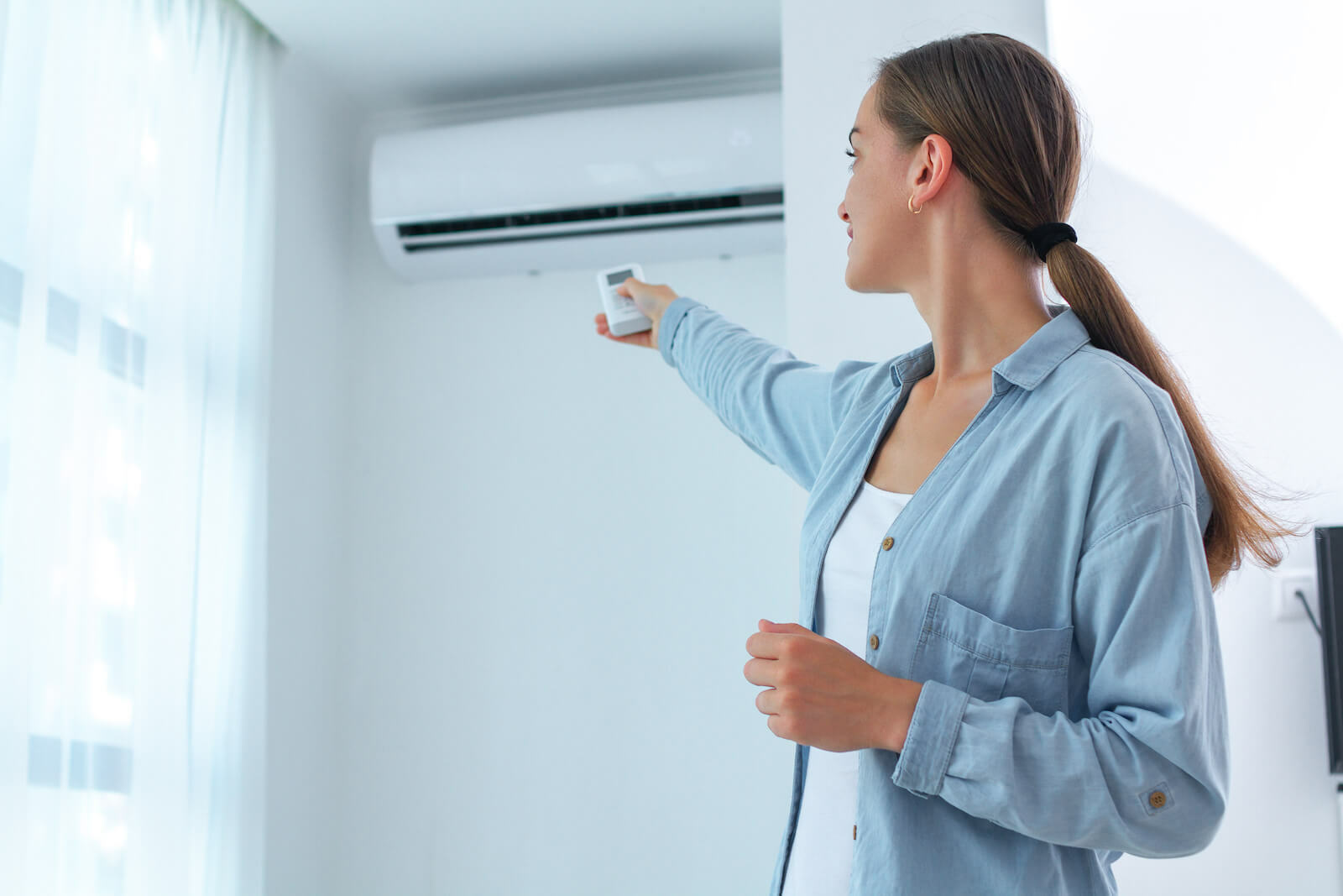 How to cool down: woman adjusting the aircon temperature