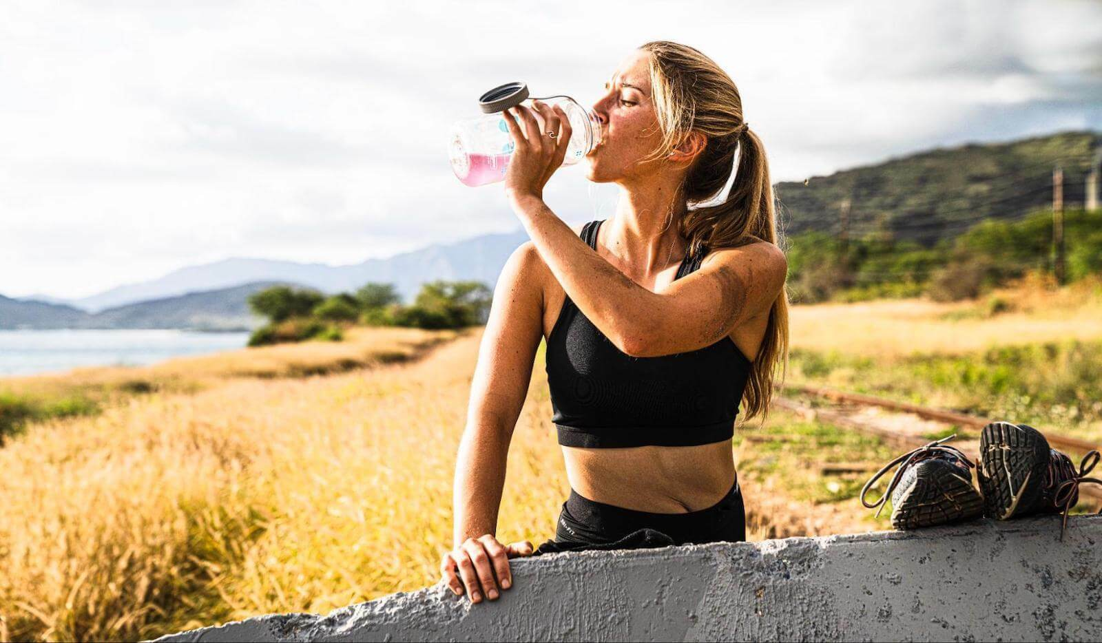 Head feels hot: woman in the fields drinking from a tumbler