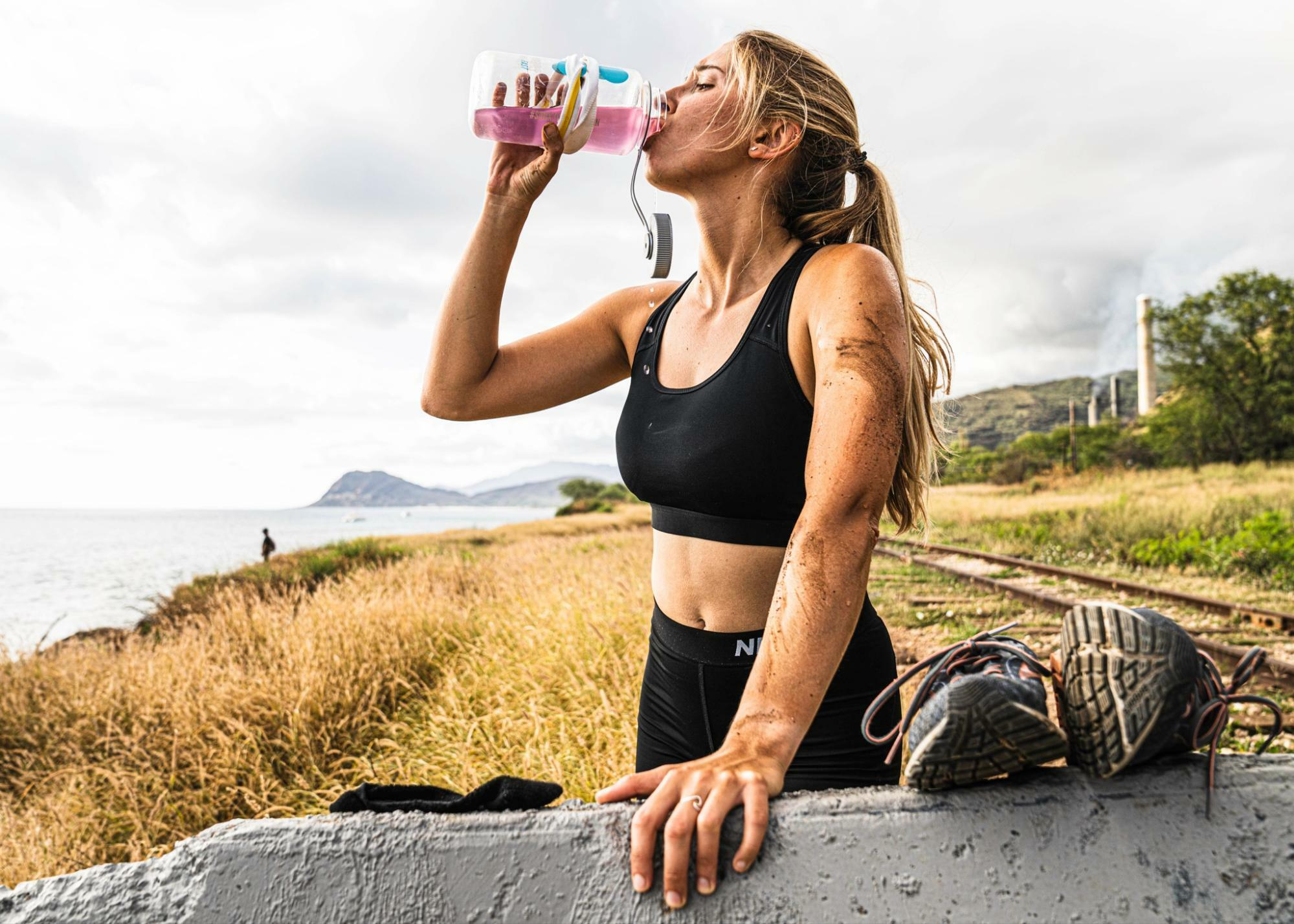 does coffee count as water: woman drinking in her DripDrop ORS bottle