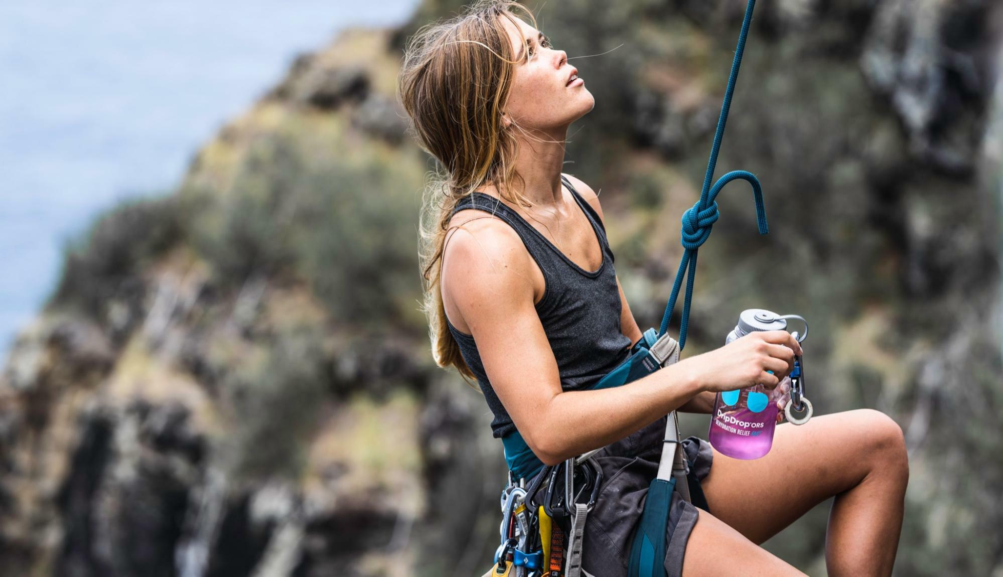 woman in a rappel holding a DripDrop ORS bottle