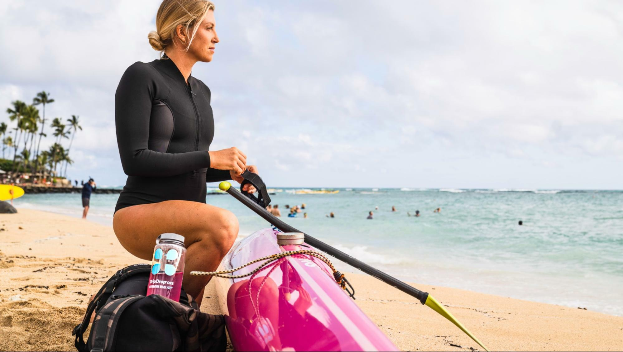 best water to drink for health: woman on the beach with a DripDrop ORS bottle on her side