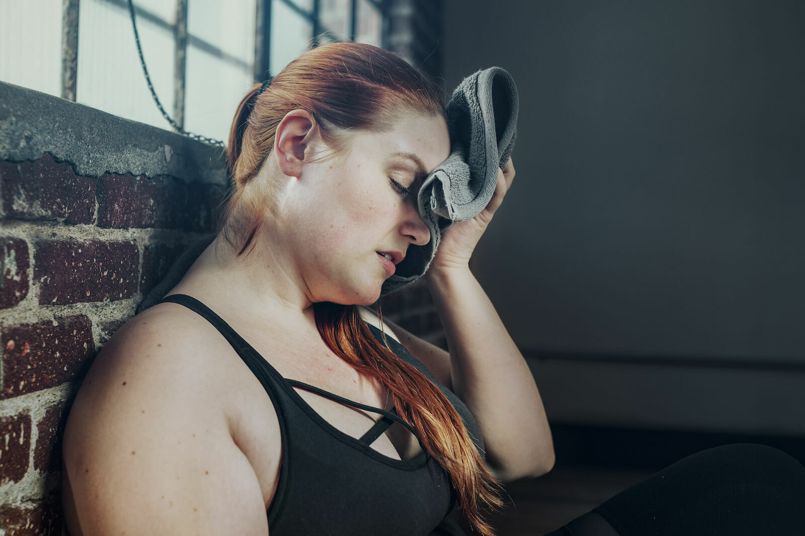 Chills and sweats: woman wiping away her sweat