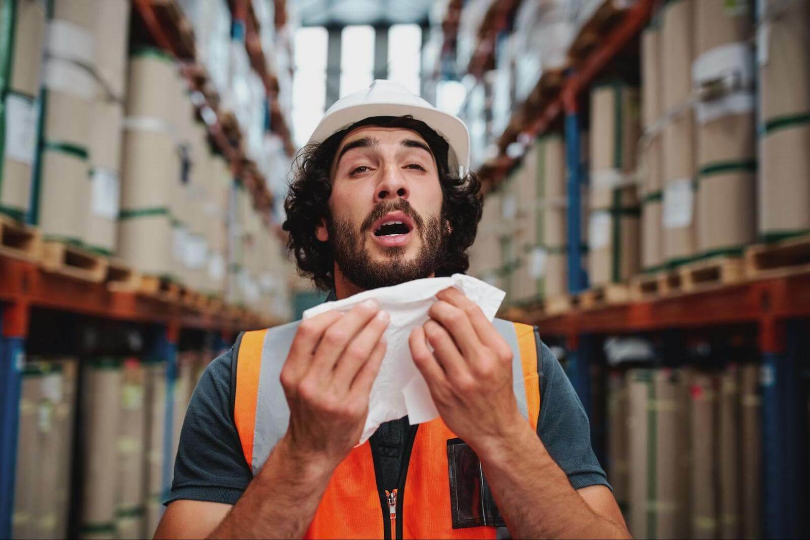 Can you sweat out a cold: worker about to sneeze into a tissue